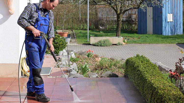 A man pressure washing a patio