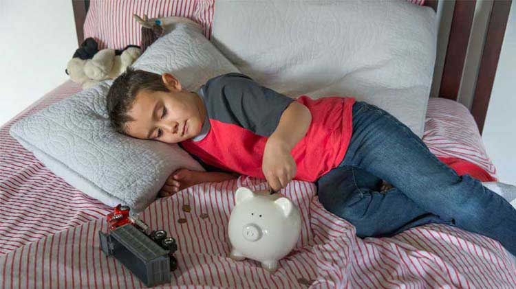 Boy on bed with his piggy bank