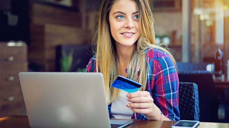 Woman entering a credit card number online.