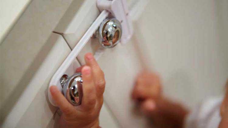 Toddler hands on secured cabinet handles