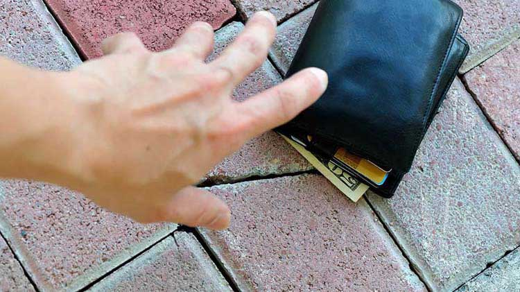 Hand reaching for wallet on ground