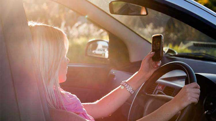 Young driver looking at her phone while driving