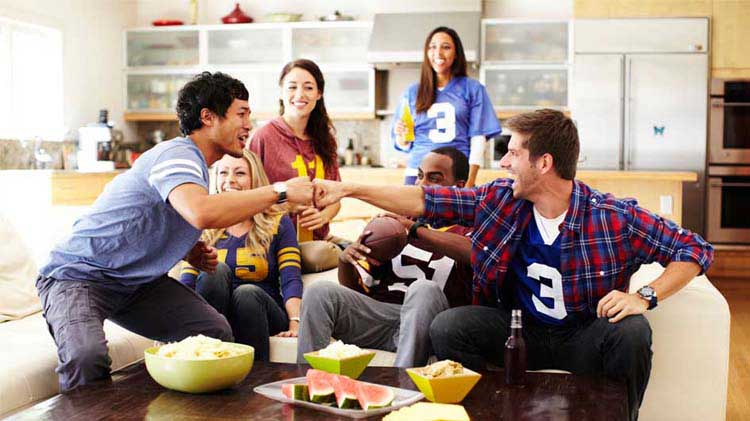 Sports fans fist bumping on a couch with snacks
