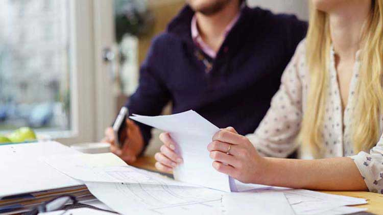 Couple seated with paperwork