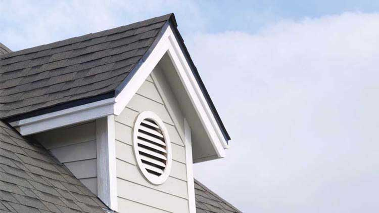 An attic gable with a circular vent.