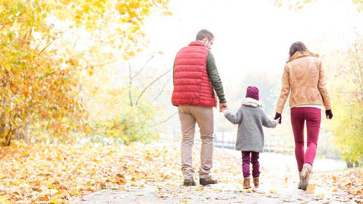 Parents holding their kid's hand walking down a leafy lane in the fall