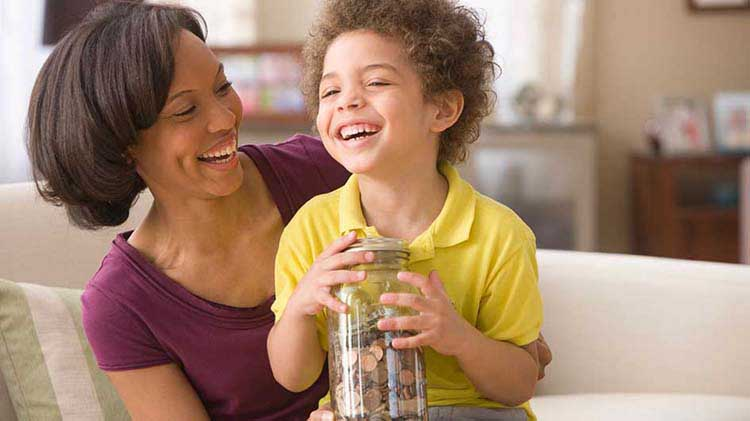 Mother with young boy holding jar with coins.