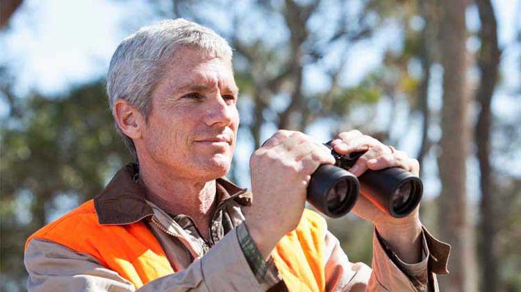 Hunter with orange vest and binoculars.