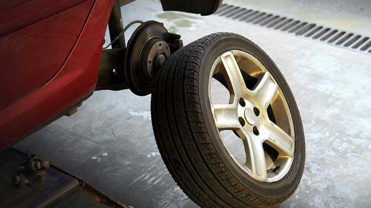 A car tire is removed to show the brakes underneath.