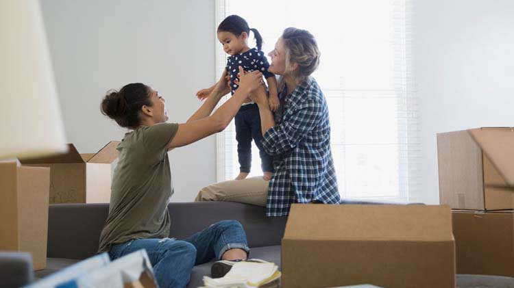 Two women and a little girl playing in a room full of moving boxes