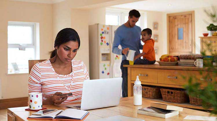 Woman working on laptop with family in the kitchen
