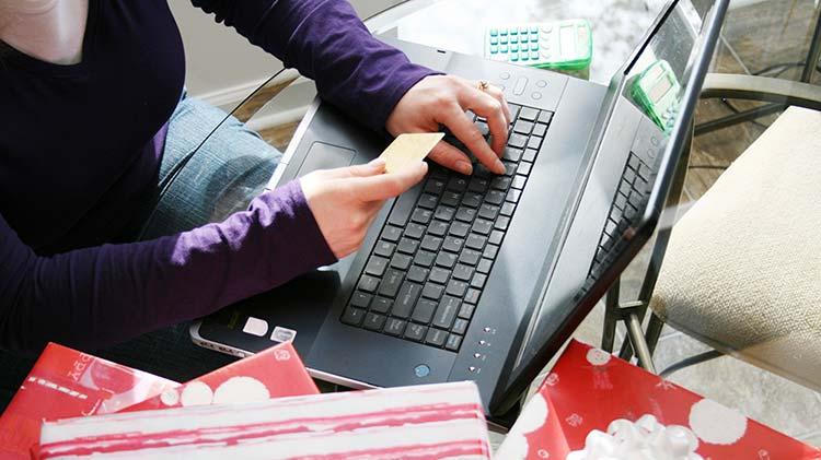 Mujer con una tarjeta de crédito en la mano y trabajando en el computador