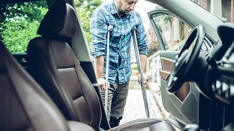 Man on crutches enters his car and is thankful he has Personal Injury Protection.