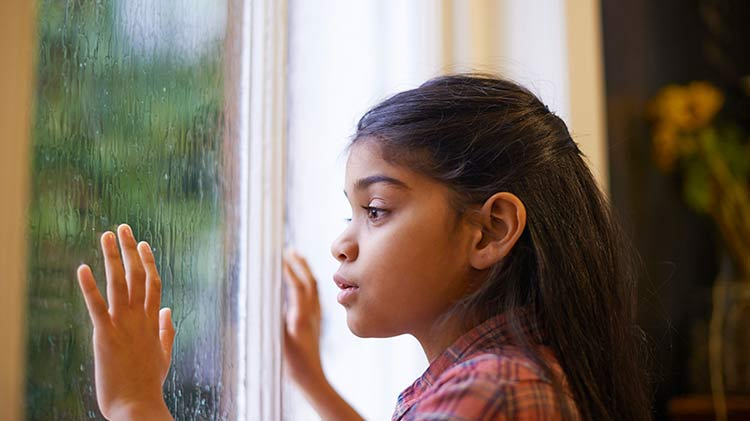 Girl safely looking out a rainy window