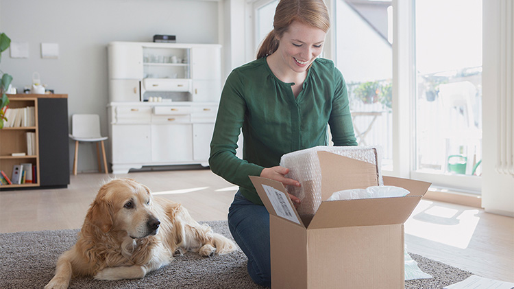 Woman unpacking box of ordered goods