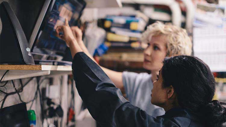 Two woman pointing at a monitor to better understand questions for the mechanic