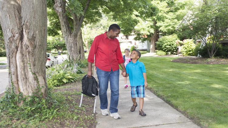 Boys and adult walking on sidewalk on their way to school.