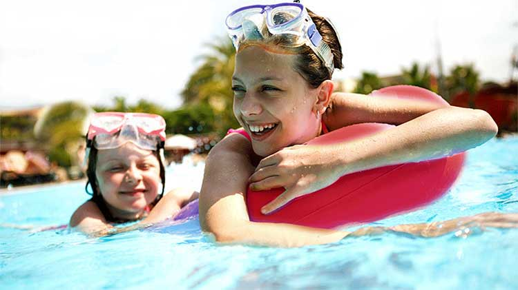 Two happy young girls in a swimming pool.