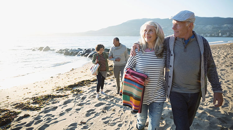 Retired couple enjoying travel retirement milestone, walking on the beach