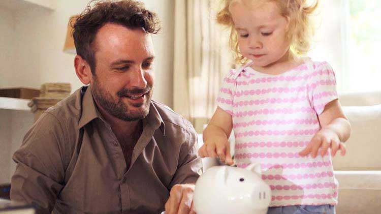 Man and young daughter putting money in piggy bank
