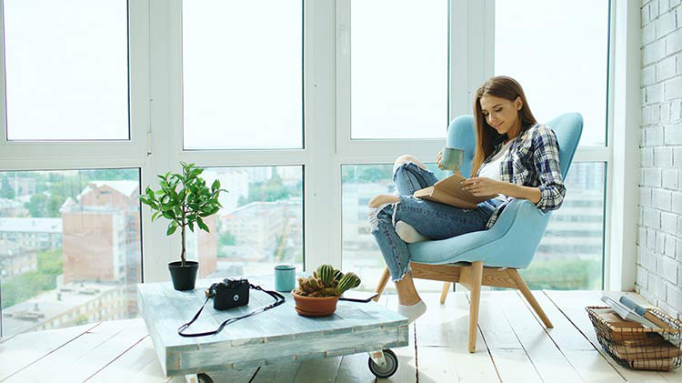 Woman reading in chair in front of window, looking happy due to buying a condo