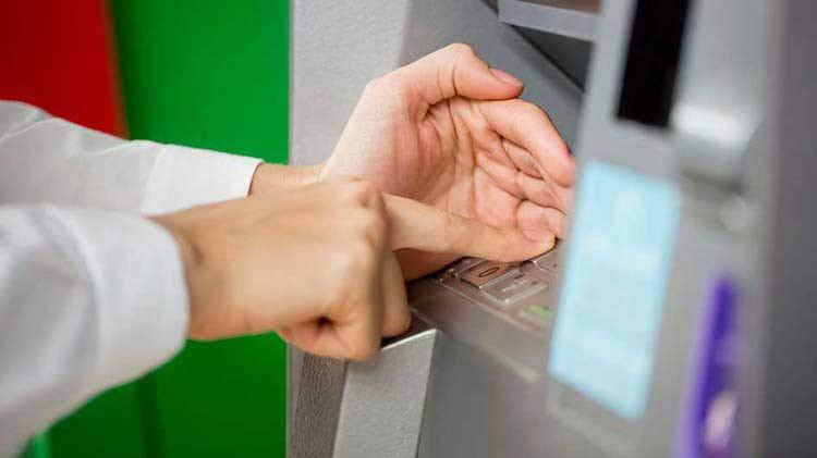 Person's hand entering a PIN number at an ATM machine.