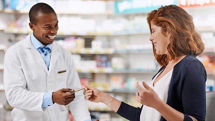 Smiling woman paying pharmacist with a credit card.