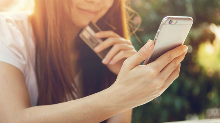 A woman looks at her phone while holding her credit card