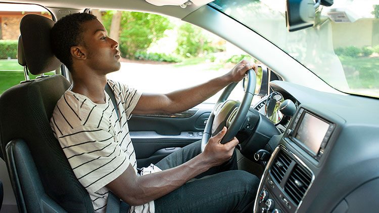 A young man is driving his car, wearing his seat belt and practicing defensive driving