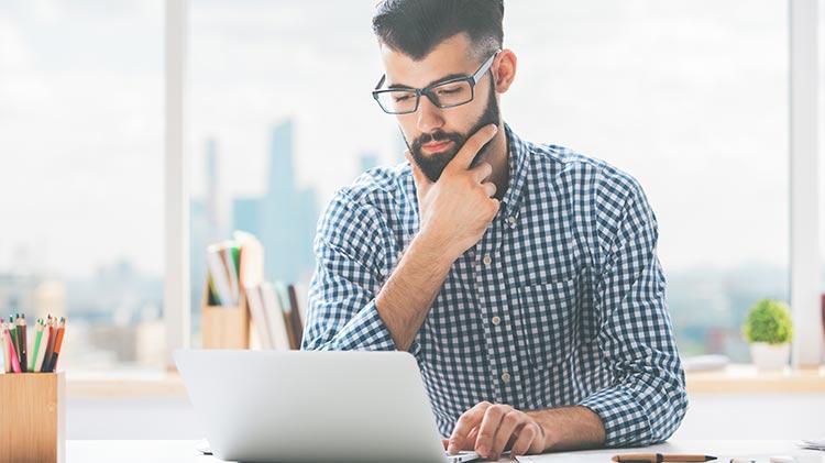 Un señor trabajando en su estrategia de creación de contenido y usando su computador portátil