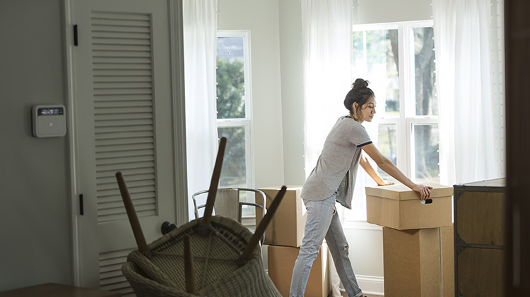 A woman leans against a packing box while packing to move after her divorce