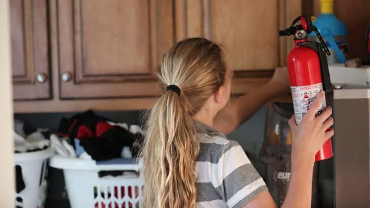 Una niña poniendo un extintor en un gabinete de lavandería