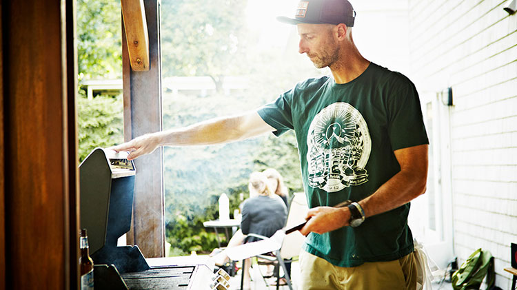Man grilling to minimize exterior fire risk