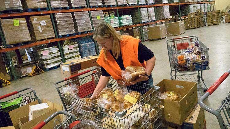Durante el día del buen vecino, una mujer clasifica comida en cajas y canastas en un banco de alimentos.