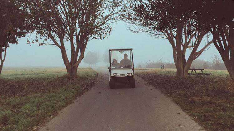 Man on a foggy golf course driving a golf cart