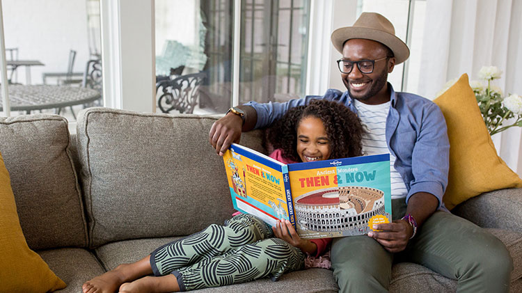 A man and his daughter are sitting on the couch reading a book