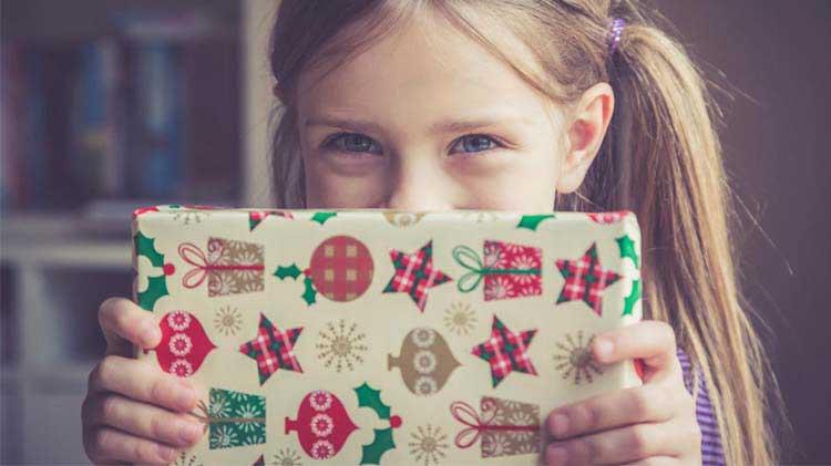 Little girl holding christmas present.