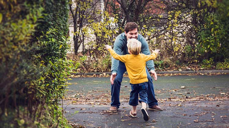 Child running into father's arms