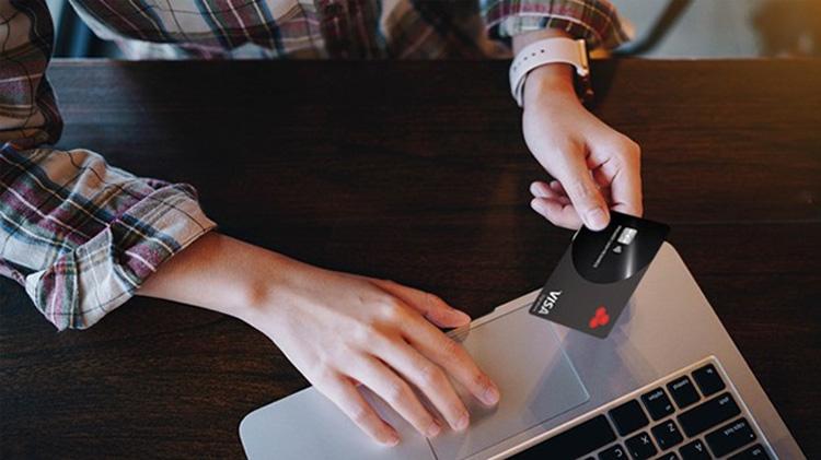 Persona usando el computador portátil para hacer una compra en línea con una tarjeta de crédito.