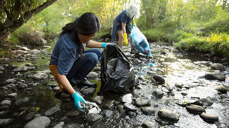 Women are picking up trash in a creek