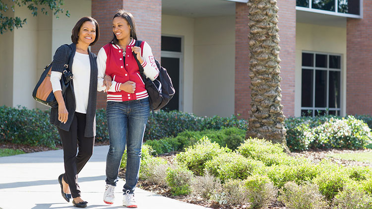 Mother and daughter walk arm-in-arm on a college tour.