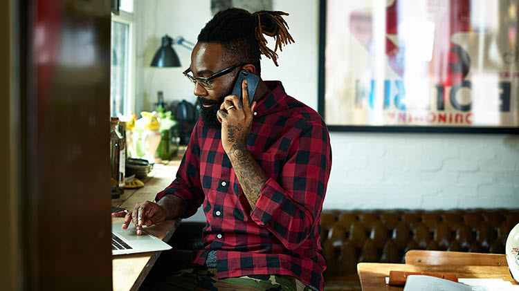 Hombre adulto trabajando en su computador portátil mientras usa el teléfono