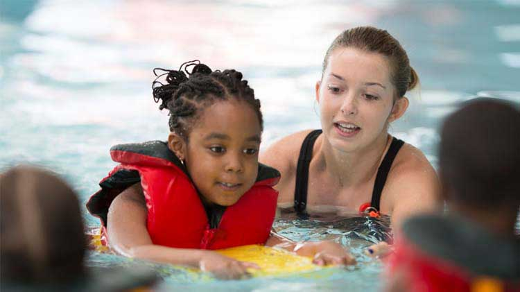 A young girl taking swimming lessons