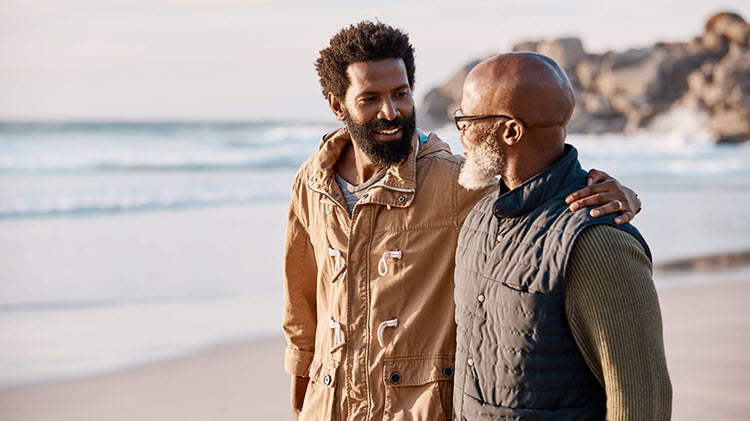 Father and son walk together on the beach and talk about money.