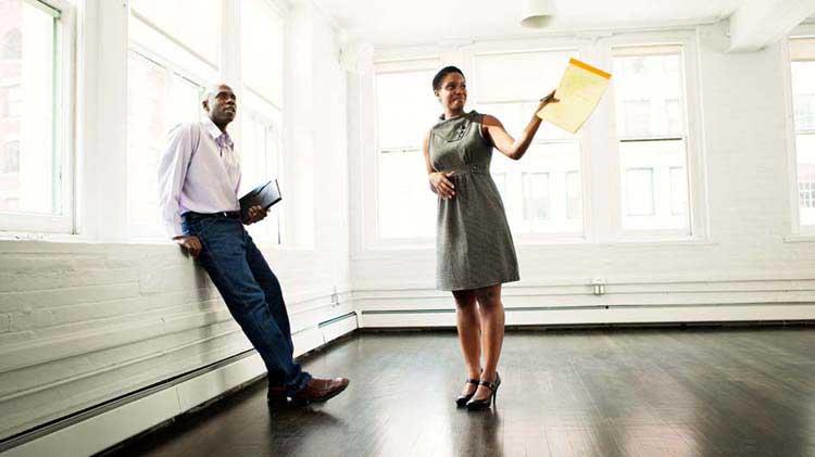 Un hombre y una mujer parados en medio de una casa vacía.