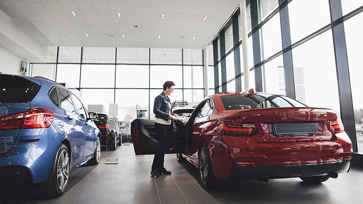 A woman looks at a new vehicle at a dealership
