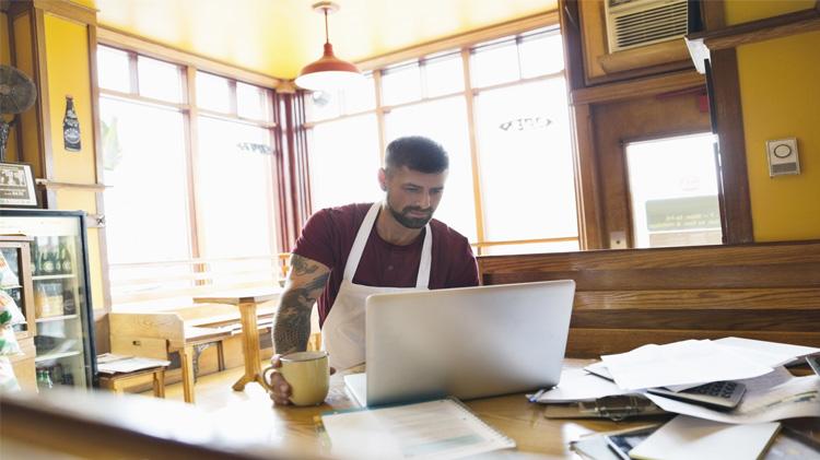 Dueño de pequeña empresa revisando sus metas empresariales en su computadora portátil.