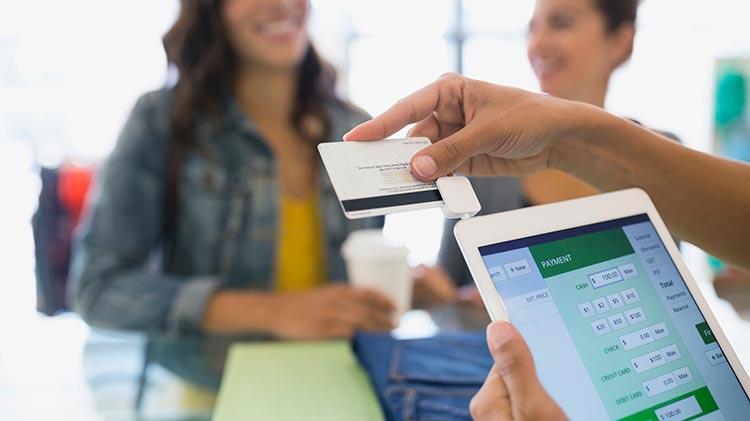 Alguien sostiene una tableta haciendo un pago con tarjeta de crédito en una tienda