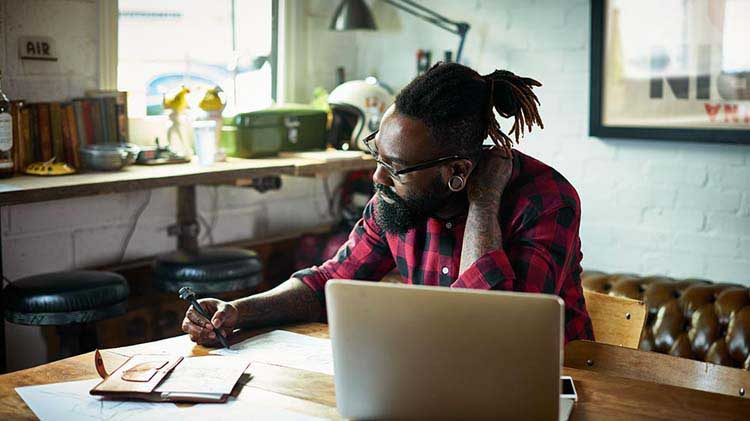 Bearded man with glasses at home desk with laptop, checking a paper document
