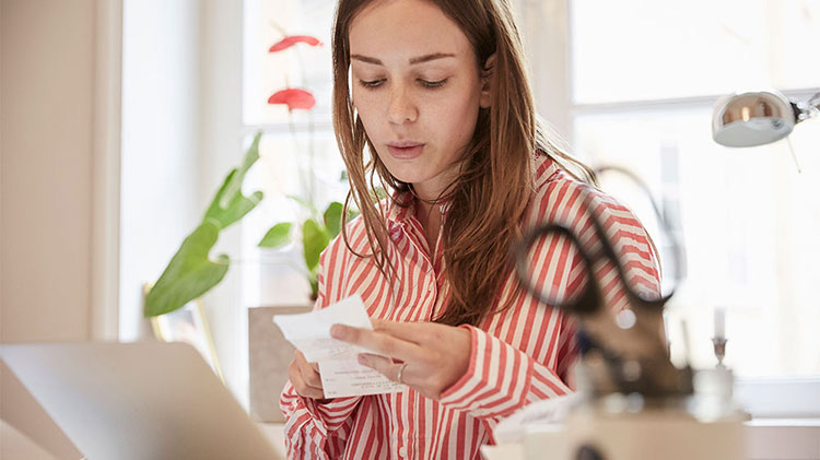 Woman checking receipt to boost savings habits